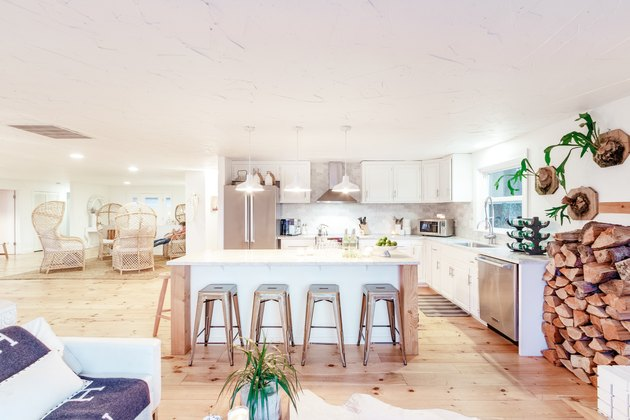 a large kitchen with an island flanked by metal stools, white cabinets, and a rustic pine floor