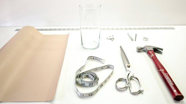 Leather sheet, measuring tape, shears, hammer, rivets, glass vase