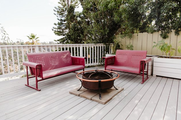 Red metal couches around fire pit on large white deck