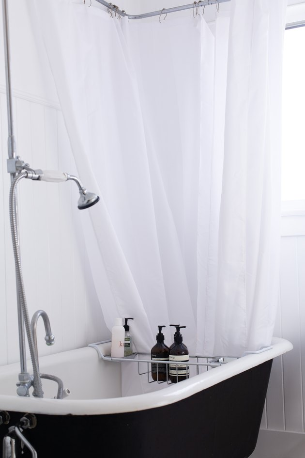 the walls, shower curtain, and most fixtures in this bathroom are white; the tub stark black