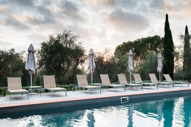Pool side lounge chairs with closed umbrellas at dusk