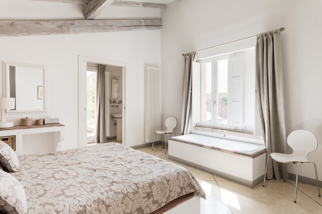 White bedroom with window bench and long curtains
