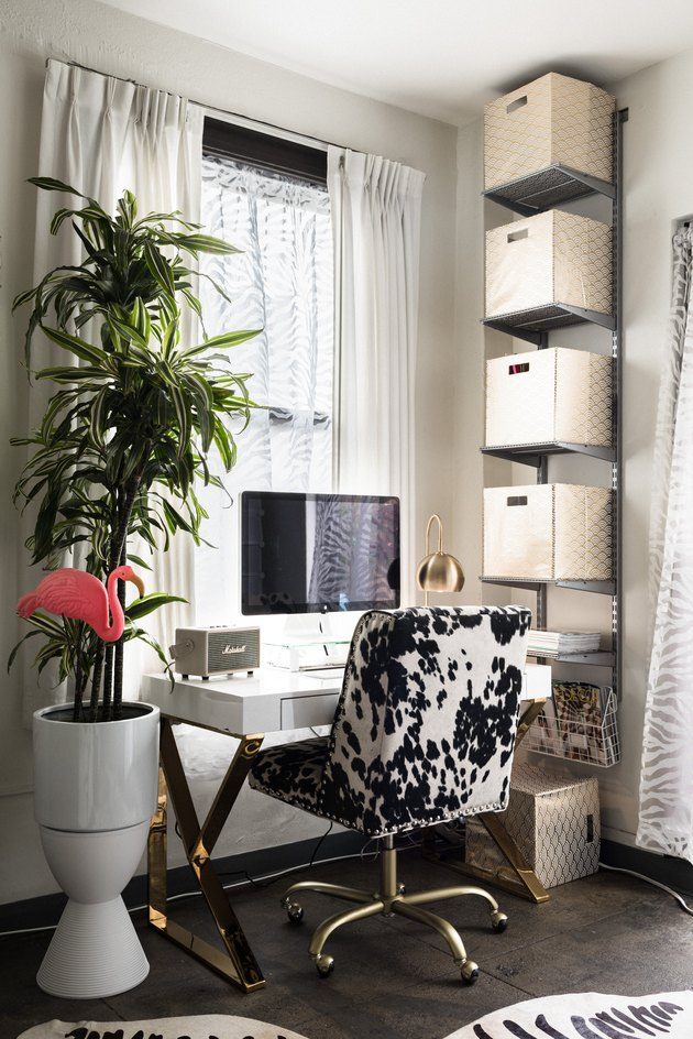 Office corner with white desk and cube shelves, and faux cow hide chair