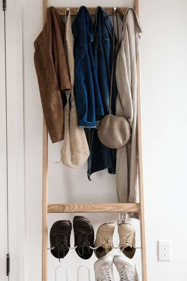 jackets and shoes hanging on a wooden coatrack