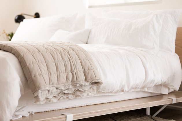 a platform bed made from birch plywood panels with white bedding