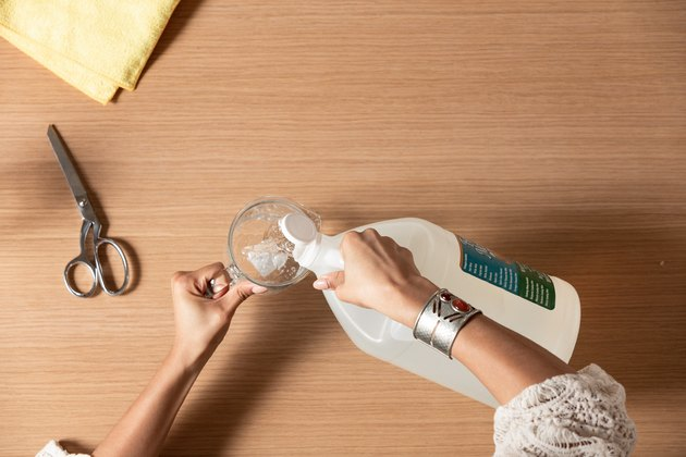 Hand pouring liquid from plastic jug into measuring cup next to scissors and yellow dryer sheets against wood countertop