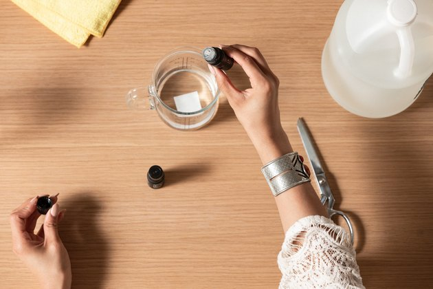 Hands dispensing clear liquid with eyedropper into glass measuring cup next to silver scissors and yellow dryer sheets on wood countertop