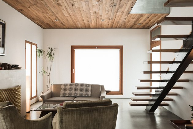 industrial farmhouse wood paneled ceiling, concrete floors, modern staircase, couch, chairs, large window.