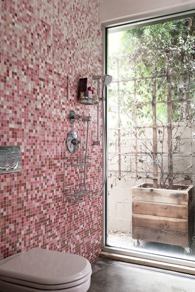 pink mosaic shower tile in an open shower, glass door leading to a back patio, white toilet