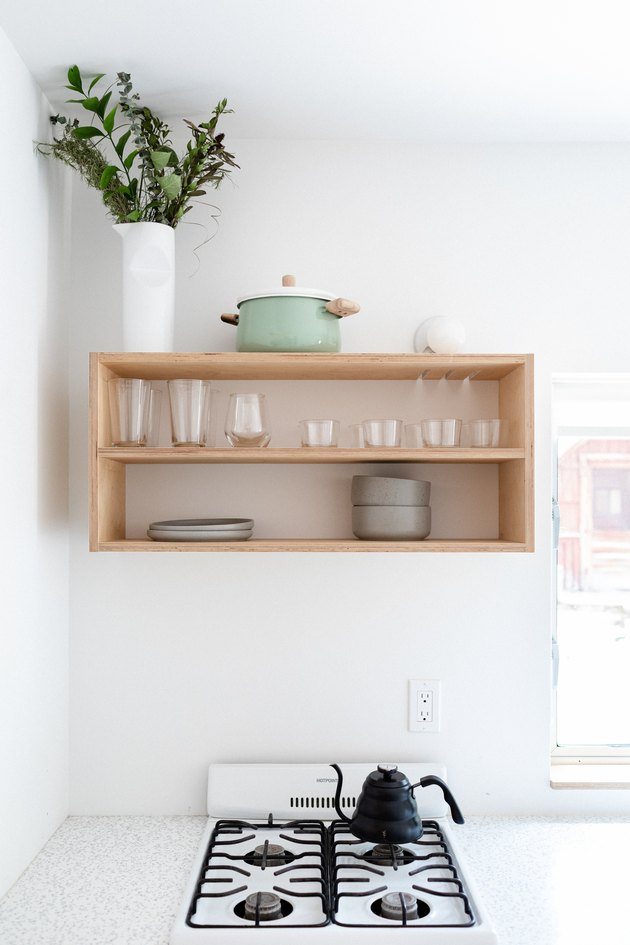 A minimalist white walled kitchen and wood shelving with dishware and plant and apartment size stove