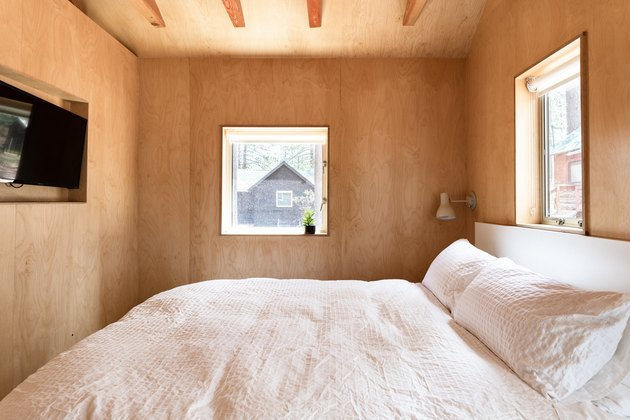 small spaces minimalist wood-walled bedroom with small windows and white bedding