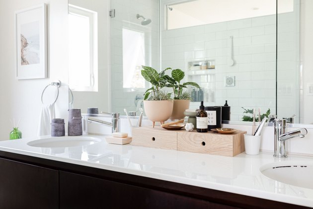 white bathroom countertop with dark wood cabinets and plywood storage box and modern plant and chrome faucet
