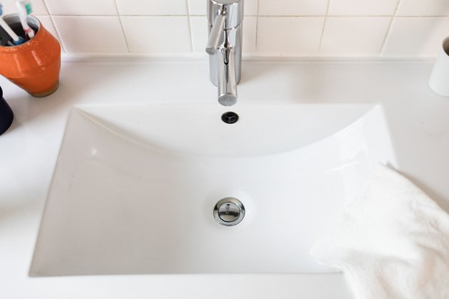 closeup of white sink with silver single-handle faucet