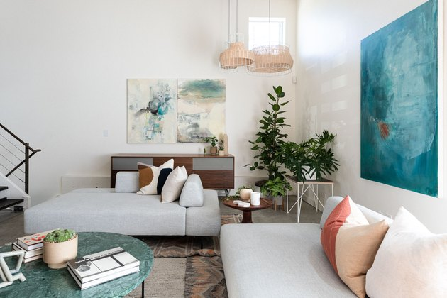 Modern-contemporary living room with couches, pillows, paintings, plant, marble-top coffee table, and white stairwell against white walls