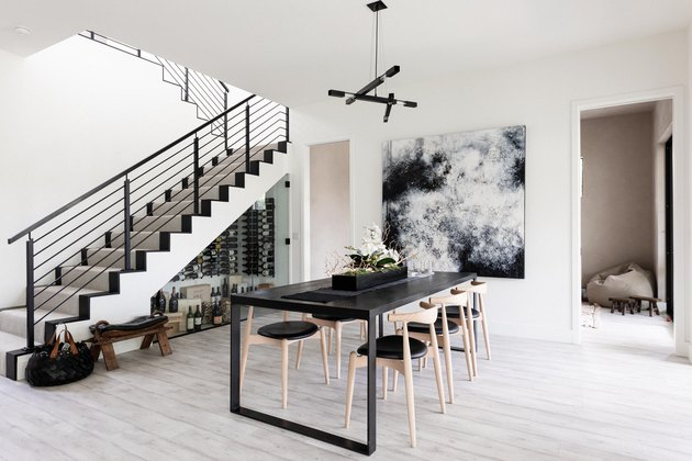 Dining room with gray wood floors, black furniture, contemporary art and staircase