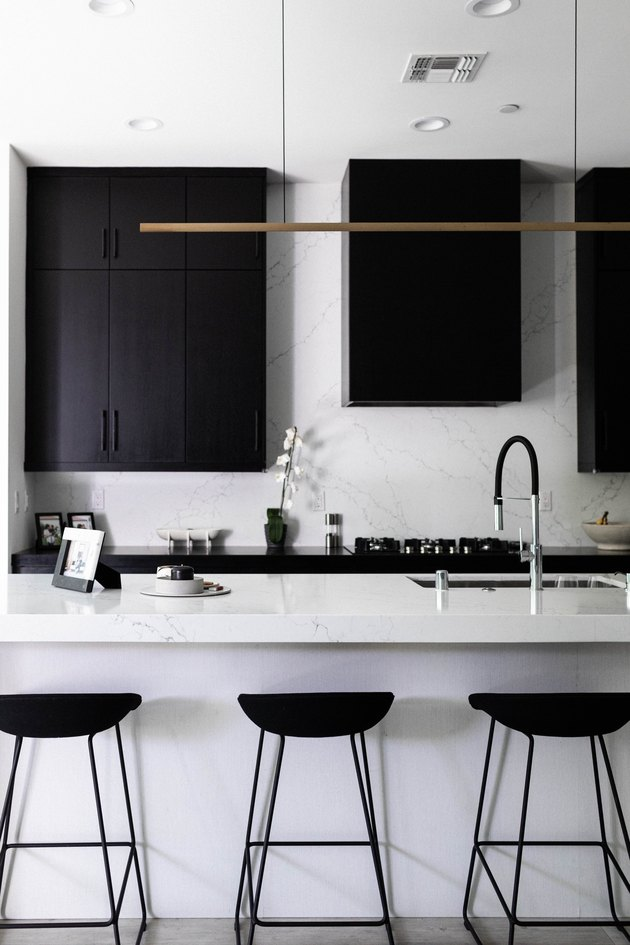 Minimalist kitchen with white counters and black cabinets and stools