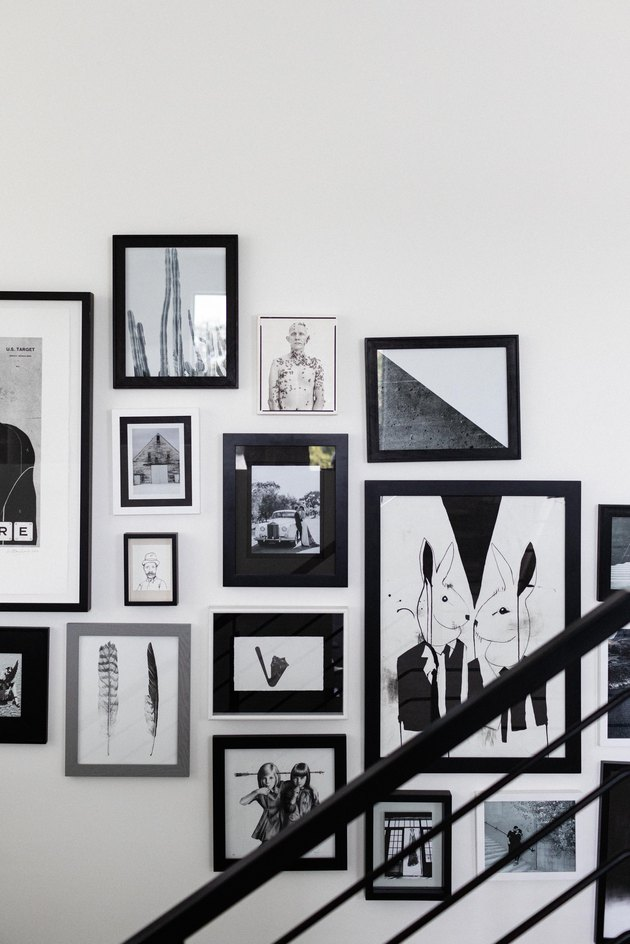 Art framed in black frames on a wall next to a black banister