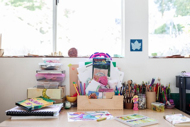 A kid's art table with various supplies facing windows