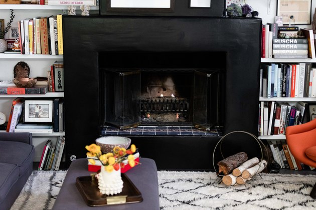 Black Room Ideas with Black mantle and fireplace with built in shelving, area rub, books, coffee table.