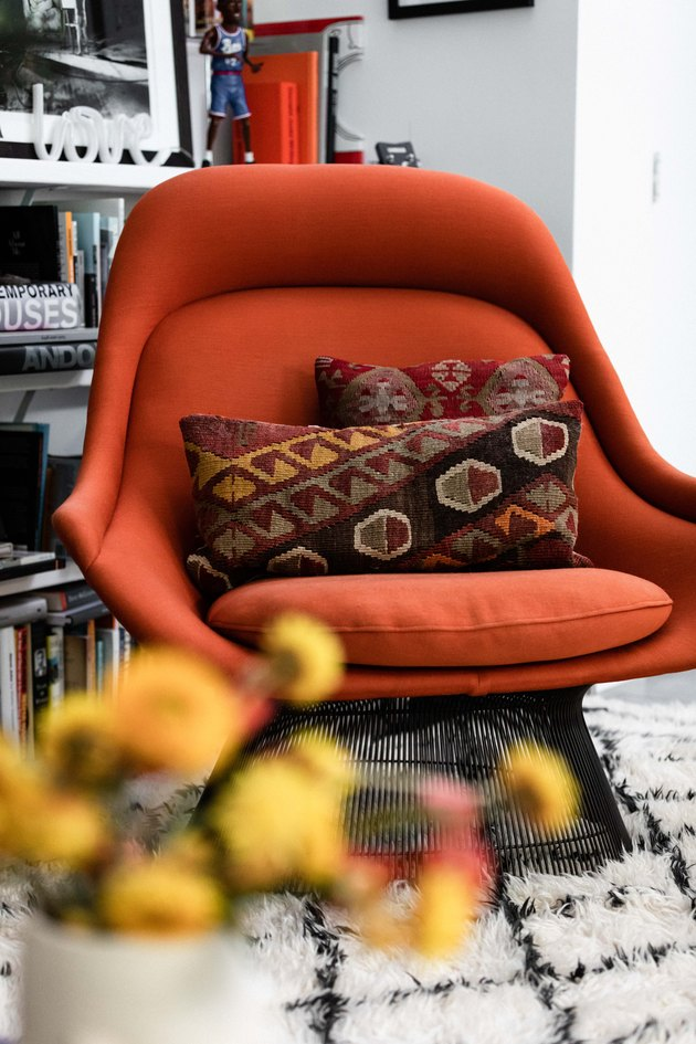 orange midcentury accent chair with brown patterned pillow