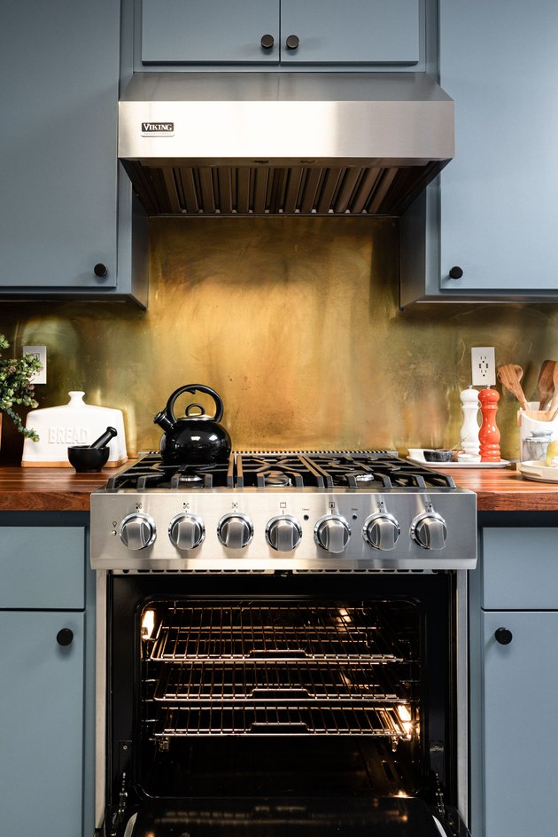 Brass backsplash behind stove in kitchen with blue painted cabinets.