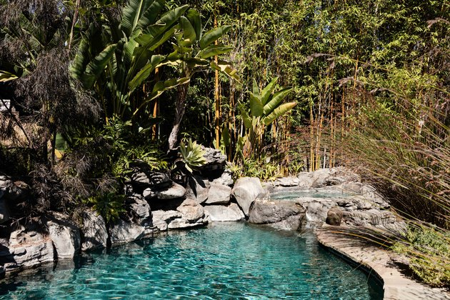An in-ground pool surrounded by rocks and a natural green setting
