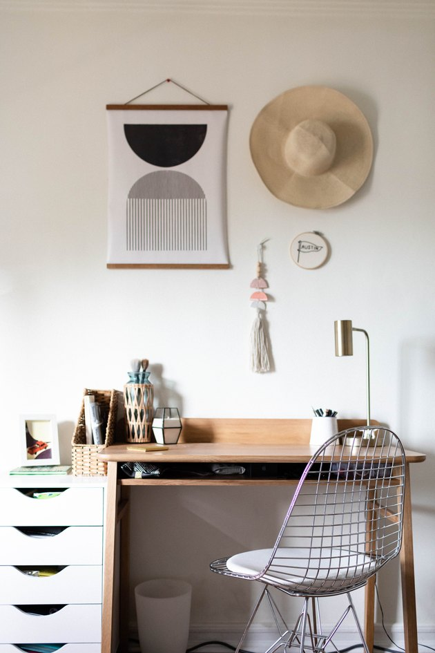 A wood desk with white drawers and a retro wire chair