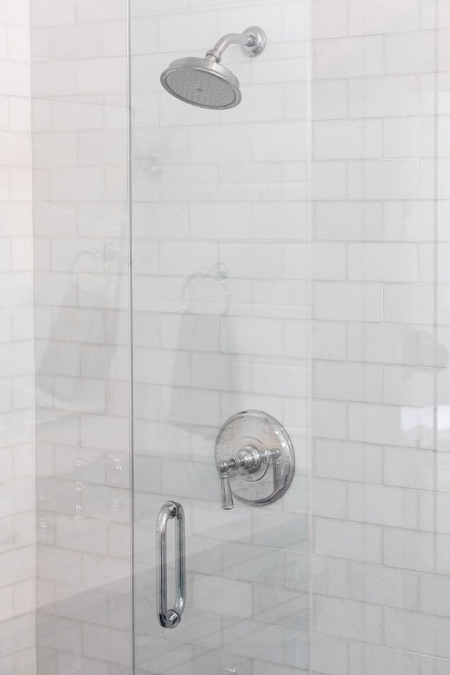 white subway tile, glass shower door, silver showerhead and handle
