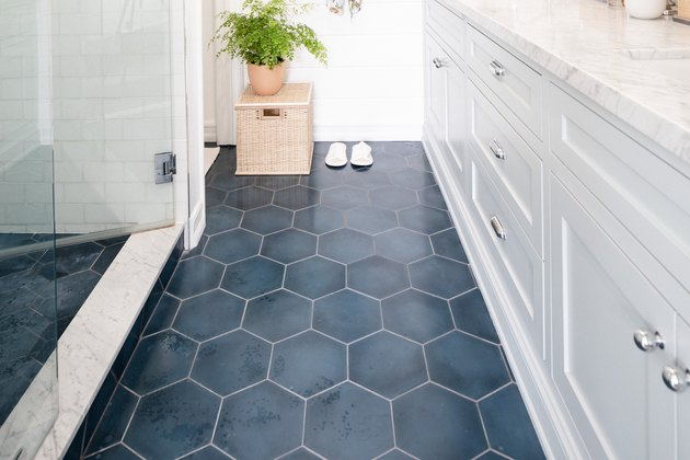 Bathroom floor with blue tile and plant on a basket