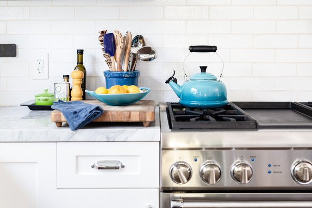 Fireclay white tiles behind stove in kitchen with blue kettle.