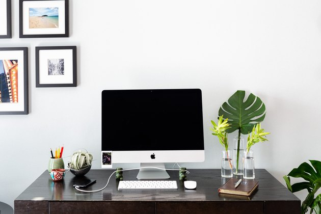 desk with apple desktop computer, plants, decor, and picture frames