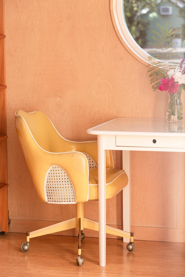 yellow leather desk chair and white small desk with flower vase on top