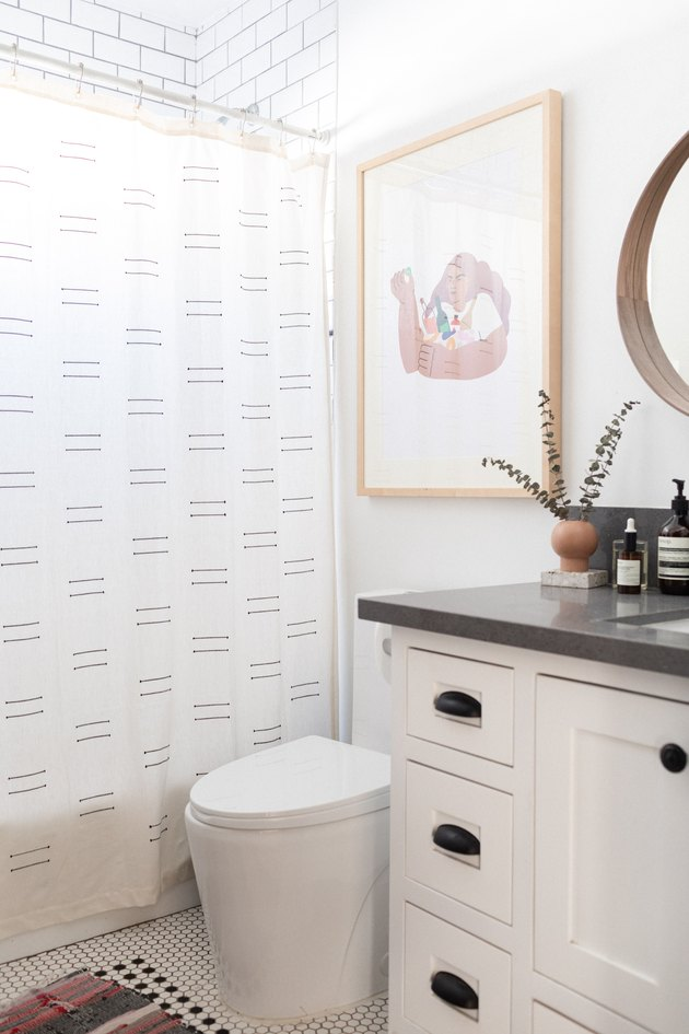 eco-friendly bathroom idea for white space with vanity and shower, art hanging above the toilet