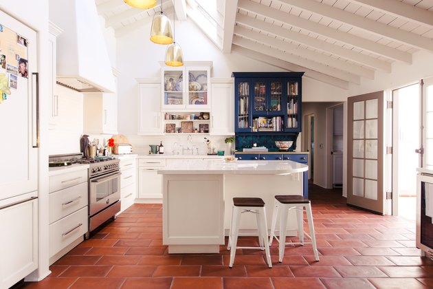 white kitchen with terra cotta tile and exposed wood beam ceiling