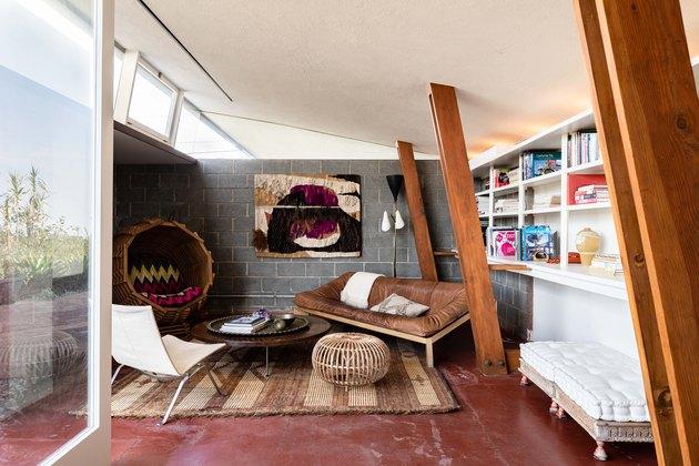 Mid-century living room with maroon floors, wood beams and gray walls