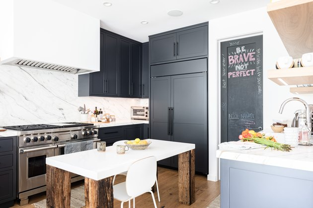 White walled kitchen with gray cabinets and wood floor