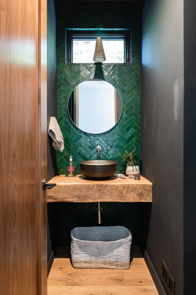 Green tiled basement bathroom idea with a wood counter and flooring with small window