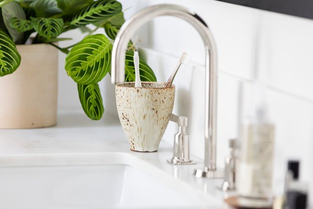 Sink on a vanity countertop with potted plant and ceramic cup with toothbrushes