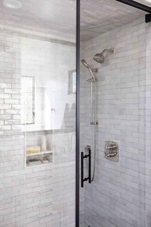 Glass shower doors with gray tiled walls