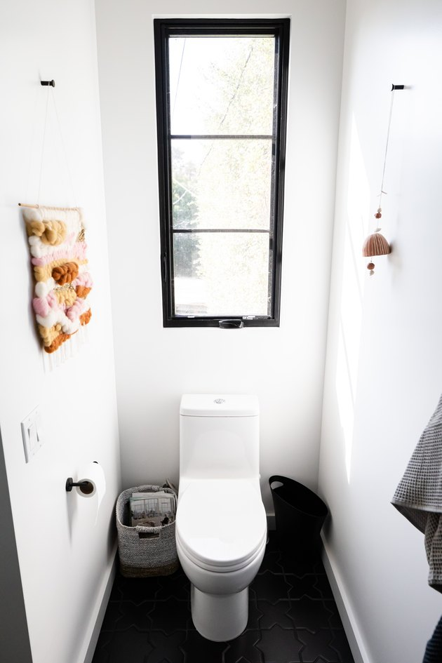 White-walled bathroom with a long black framed window over a toilet