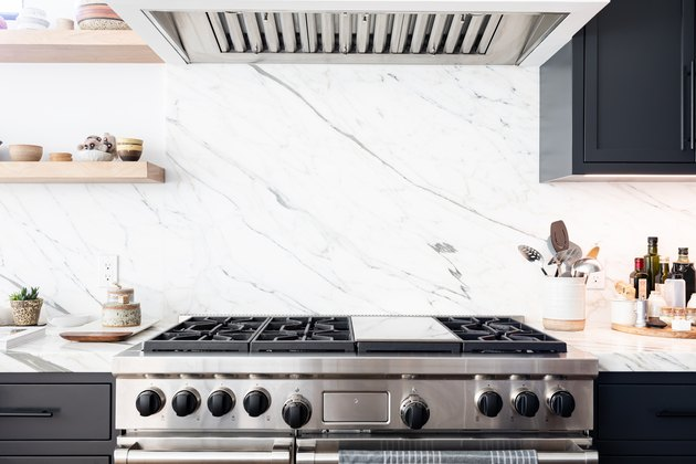 Stove with marble backsplash and vent hood