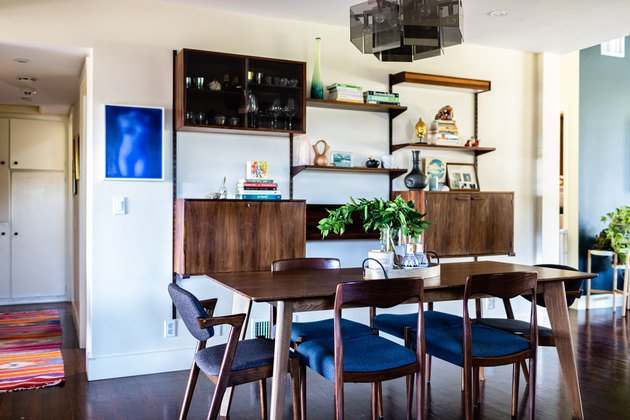 dining room wall decor idea with wood furniture and blue cushioned chairs and a wood sideboard