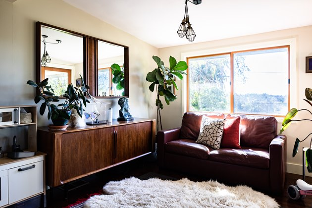 A boho styled living room with cushions, wood sideboard and plants