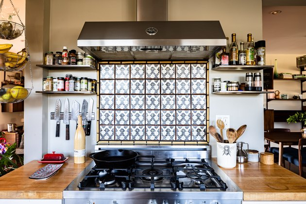 Kitchen with stainless steel oven and oven hood with tile backsplash and gray walls, and shelving on both sides and wood countertop