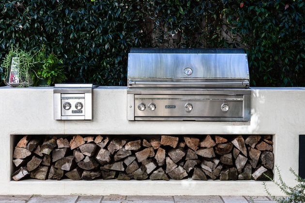 A stainless steel patio grill with firewood