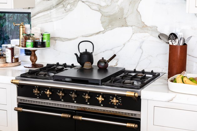Black Room Ideas with Stovetop with teapots in a kitchen with white countertops and granite backsplash