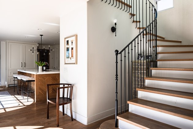 A wood stepped staircase idea with black railings in a white-walled house