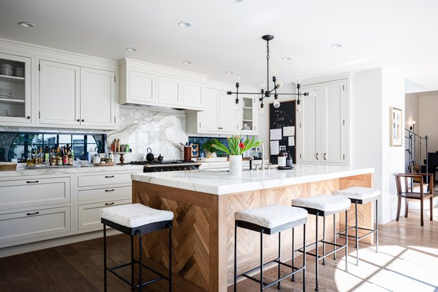 A kitchen with stove vent, white cabinets, contemporary light fixture and wood kitchen island