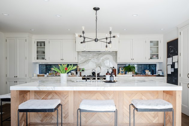 Wood kitchen island, white cabinets and a contemporary light fixture