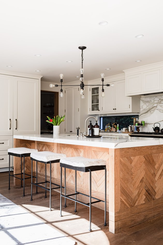 A wood kitchen island with a contemporary light fixture and white walls